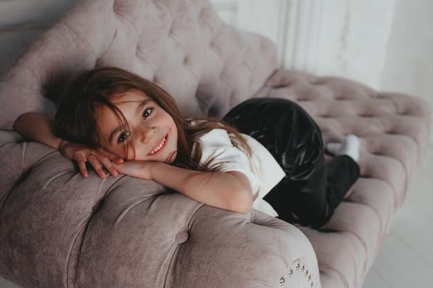 Süßes mädchen liegt auf dem sofa auf dem weißen wandhintergrund