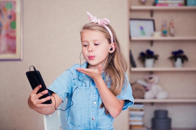Süßes mädchen mit smartphone, das einen luftkuss bläst