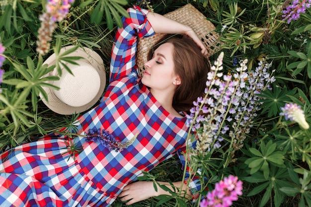 Süßes mädchen schläft in einem wiesengras voller lupinenblumen.