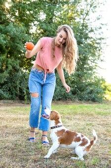 Süßes mädchen spielt mit ihrem hund im park
