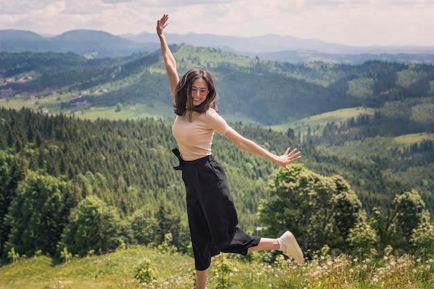 Süßes mädchen springt vor dem hintergrund der berge und wälder