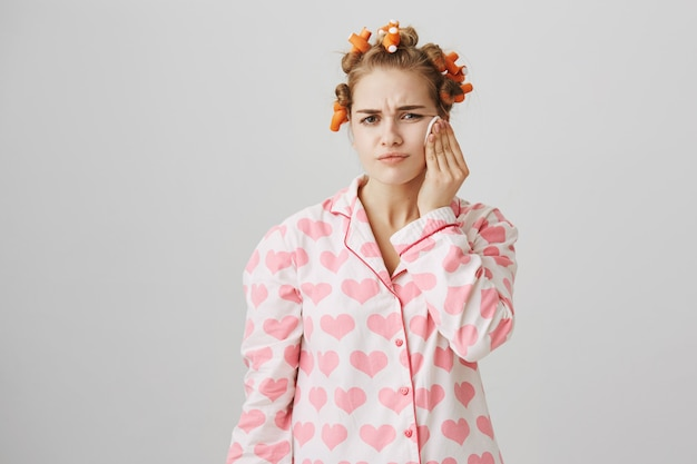 Süßes mädchen tragen reiniger vor dem schlafengehen mit wattepad auf, tragen lockenwickler und pyjama