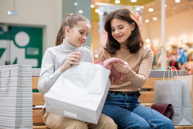 Süßes mädchen und ihre mutter besprechen neuen rosa schal, den sie am schwarzen freitag-verkauf kauften, während sie sich nach dem einkauf ausruhen