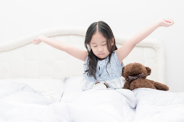Süßes mädchen wacht morgens im schlafzimmer auf