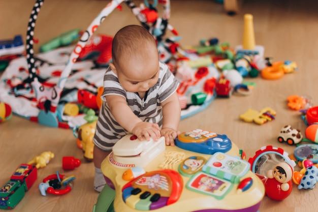 Süßes molliges baby steht und spielt mit einem kindermusiktisch. überall viele bunte spielsachen.