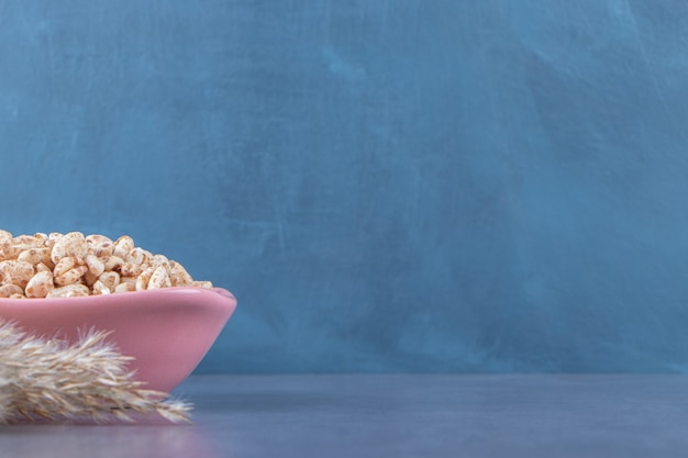 Süßes müsli in einer schüssel neben pampasgras, auf blauem hintergrund. Kostenlose Fotos