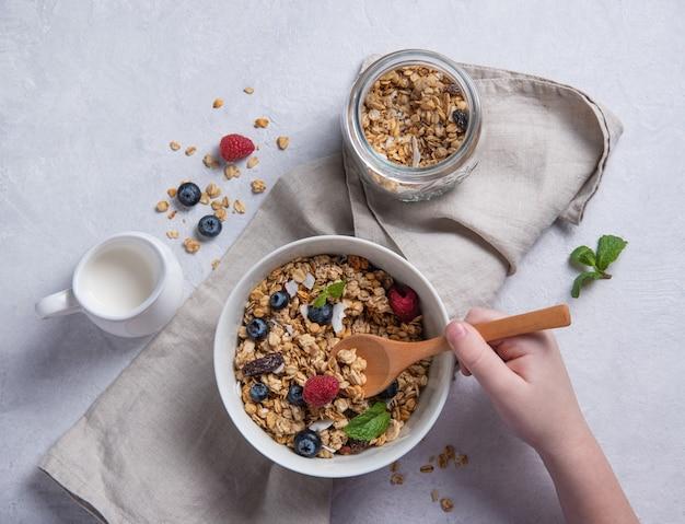 Süßes müsli mit himbeer-, blaubeer- und kokosmilch in weißen teller auf hellgrauem tisch. hände kind halten holzlöffel. energie und veganes frühstück. draufsicht
