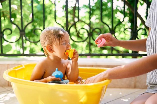 Süßes nasses kind sitzt in einem becken und nagt an einer gummiente