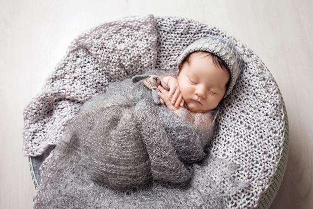 Süßes neugeborenes baby schläft in einem korb.