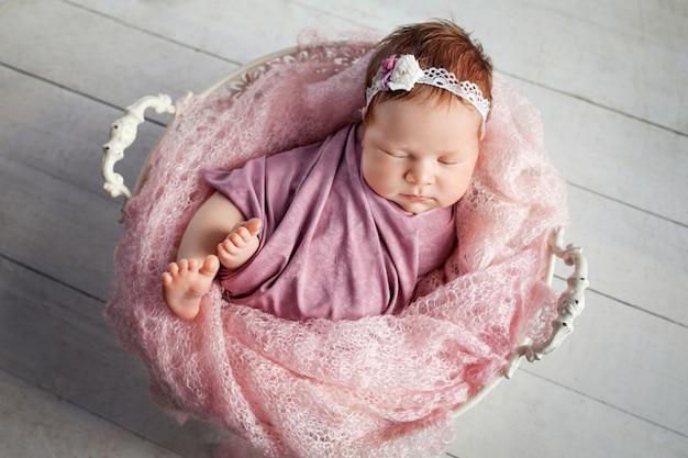 Süßes neugeborenes baby schläft mit einem spielzeug im korb.