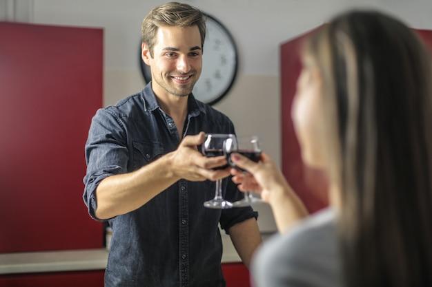 Süßes paar, das eine romantische nacht zu hause hat und mit einem glas rotwein feiert