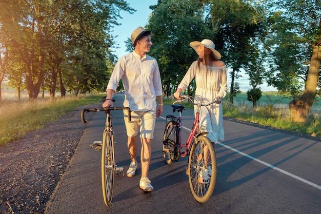 Süßes paar, das fahrräder dreht und fröhlich auf einer sommerlandstraße plaudert, die von sonnenuntergangssonne beleuchtet wird