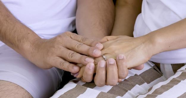 Süßes paar, das hand zusammen berührt.