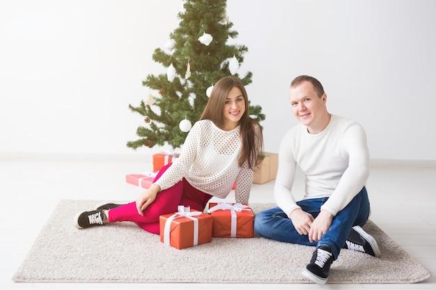 Süßes paar, das weihnachtsgeschenke öffnet und im wohnzimmer sitzt.