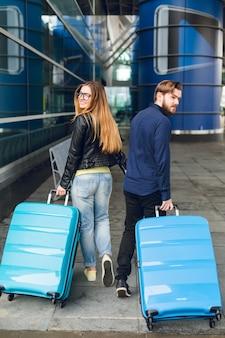 Süßes paar geht mit koffern draußen im flughafen spazieren. sie hat lange haare, eine brille, einen gelben pullover und eine jacke. er trägt ein schwarzes hemd und einen bart. blick von hinten.
