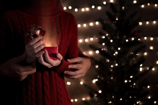 Süßes paar offene magische geschenkbox mit lichtstrahl gegen verschwommene lichter