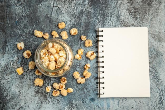 Süßes popcorn der draufsicht mit notizblock auf heller oberfläche