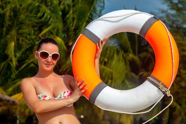 Süßes rettungsschwimmermädchen im modischen badeanzug mit großen brüsten posiert mit rettungsring. tropischer hintergrund. weibliche reise südland. porträt der lächelnden frau am strand. sicherheitskonzept des strandurlaubs