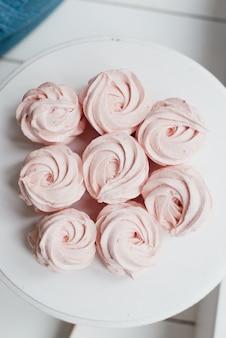 Süßes rosa baiser auf einem weißen teller auf dem tisch süßes essen