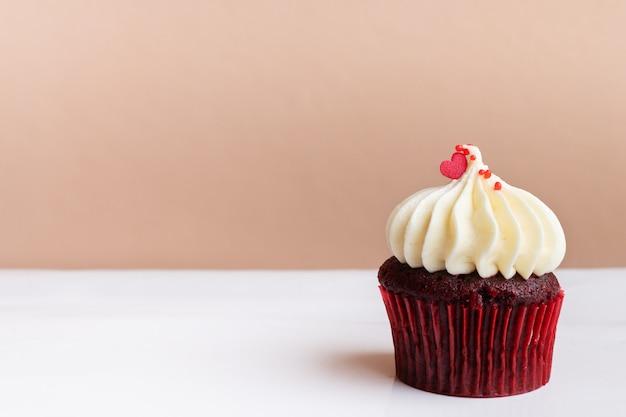 Süßes rotes herz auf weißem sahnekleinem kuchen