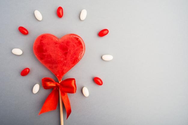 Süßes rotes süßigkeitsherzsymbol der liebe mit süßem glanzhintergrund
