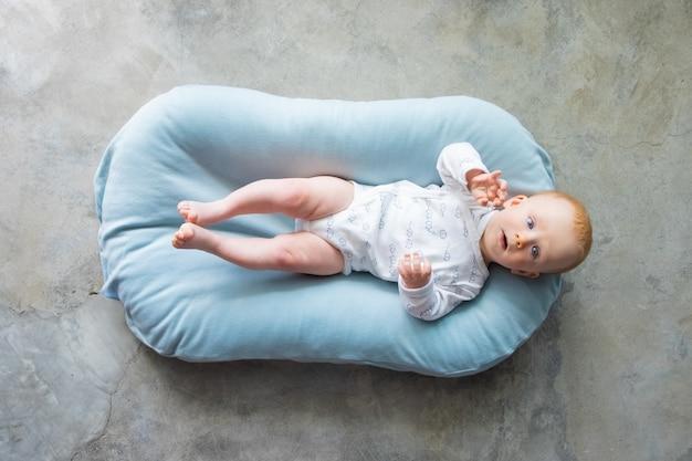 Süßes rothaariges baby, das auf rücken in der kleinen matratze liegt