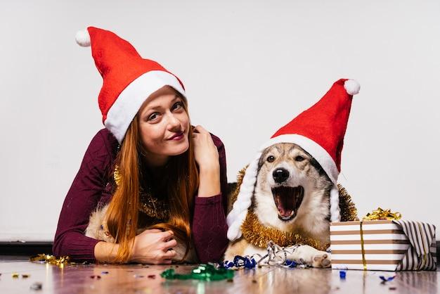 Süßes rothaariges mädchen mit einer roten mütze auf dem kopf, das mit ihrem hund auf dem boden liegt und auf das neue jahr wartet