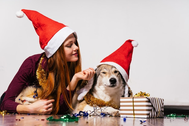 Süßes rothaariges mädchen mit einer roten neujahrsmütze auf dem kopf, das mit ihrem hund auf dem boden liegt und auf weihnachten wartet