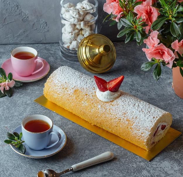 Süßes roulet mit erdbeere und schwarzem tee