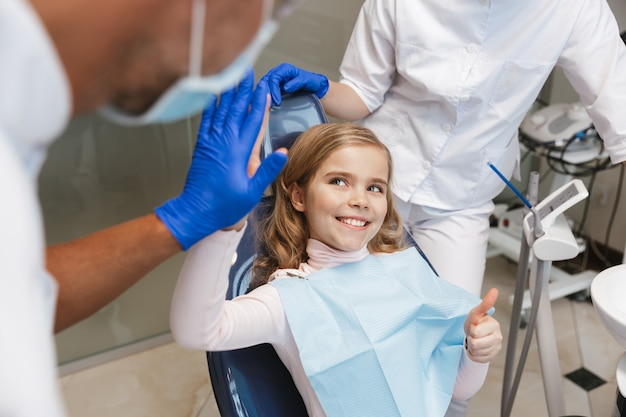 Süßes schönes kindermädchen, das im medizinischen zahnarztzentrum sitzt, gibt einander eine hohe fünf