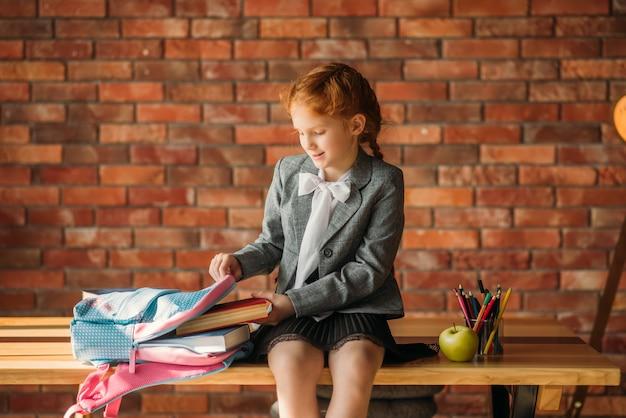 Süßes schulmädchen steckt lehrbuch in die schultasche