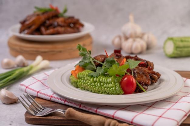 Süßes schweinefleisch in einem weißen teller mit gehackten frühlingszwiebeln, chili, limette, kürbis, tomate und knoblauch.