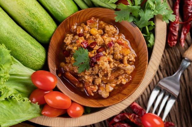 Süßes schweinefleisch in einer holzschale mit gurke, langen bohnen, tomaten und beilagen.