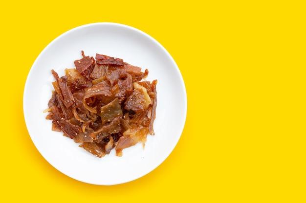 Süßes schweinefleisch oder ruckartiges schweinefleisch auf gelber oberfläche. draufsicht