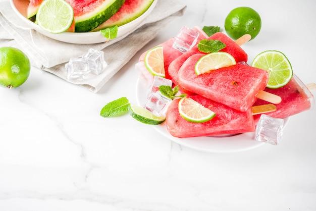 Süßes sommerwassermelonen- und -kalkeis am stiel mit geschnittener wassermelone und minze, auf weißer marmoroberfläche