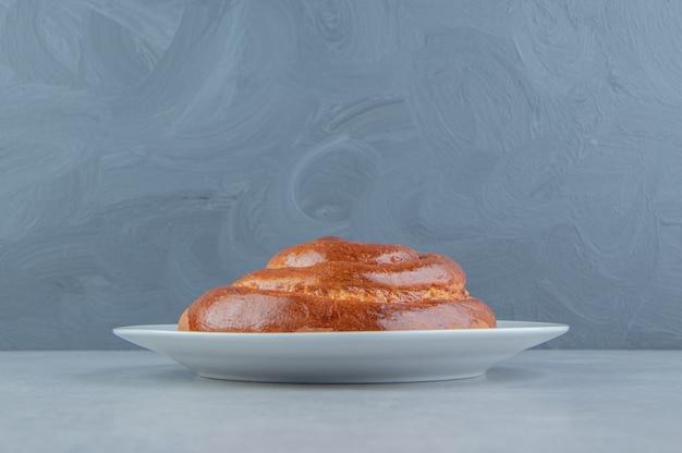 Süßes strudelbrötchen auf weißer platte.