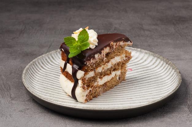 Süßes stück kuchen mit sahne und schokolade auf grauem hintergrund