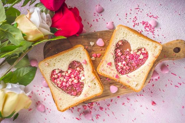 Süßes süßes frühstücks-sandwich. kreative idee für valentinstagssnack oder mittagessen. toastsandwich mit erdnussbutter und schokoladennudeln, mit valentinstagherzen rotem und rosa zucker streut draufsicht.