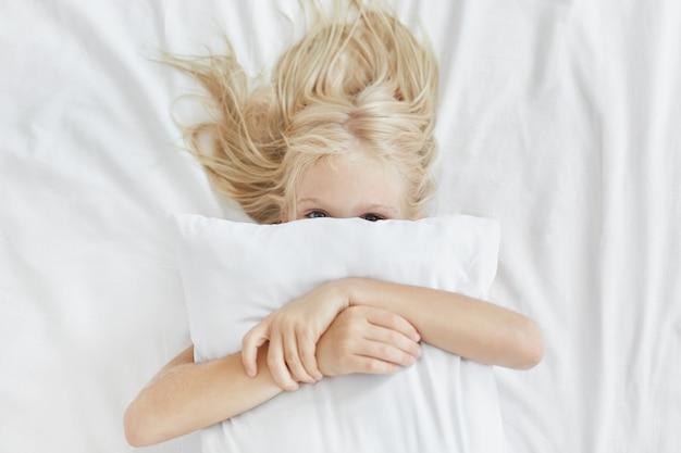 Süßes süßes mädchen mit hellem langem haar, versteckt sich hinter weißem kissen, umarmt es, während es im bett liegt und spaß am morgen hat