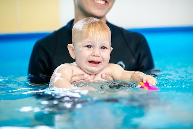 Süßes trauriges baby, das in einem speziellen pool für kleine kinder schwimmen lernt