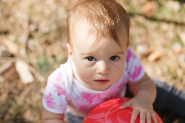 Süßes überladenes baby, das zur kamera schaut. porträt eines kindes hautnah.