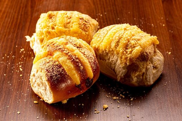 Süßes vanillecremebrot und süßes mehl auf einem braunen holztisch. es ist eine in brasilien und portugal übliche brotsorte, die aus süßem teig hergestellt wird.