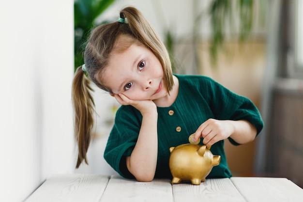 Süßes vorschulmädchen, das am tisch drinnen münze in goldsparschwein steckt