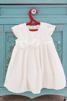 Süßes weißes kleid mit schnürung auf rotem kleiderbügel. ausstattung des kleinen mädchens mit dekorativen blumen.
