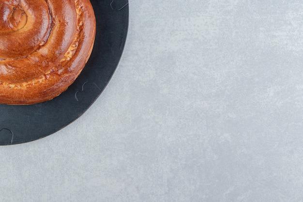 Süßes wirbelbrötchen auf holzstück.