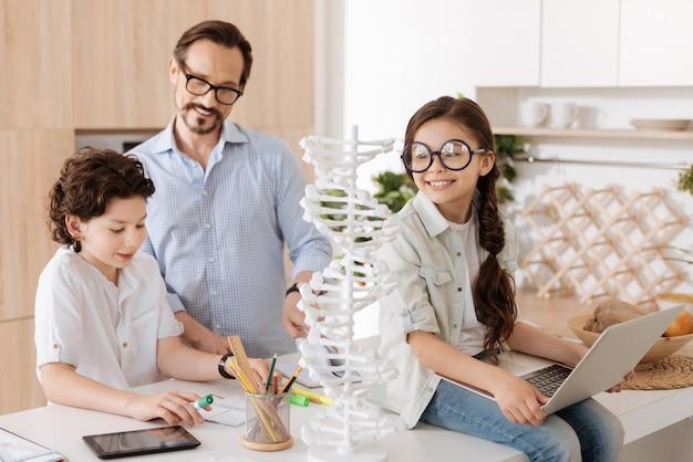 Süßes zierliches mädchen, das große runde gläser trägt, die auf der küchentheke mit laptop auf runden sitzen, während ihr vater und bruder hausaufgaben machen