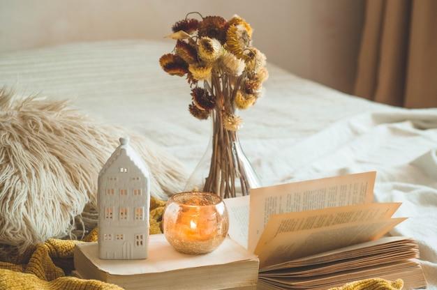 Süßes zuhause. stillleben details im innenraum des wohnzimmers. getrocknete blumenvase und kerze, herbstdekor auf den büchern. lesen, ausruhen. gemütliches herbst- oder winterkonzept.