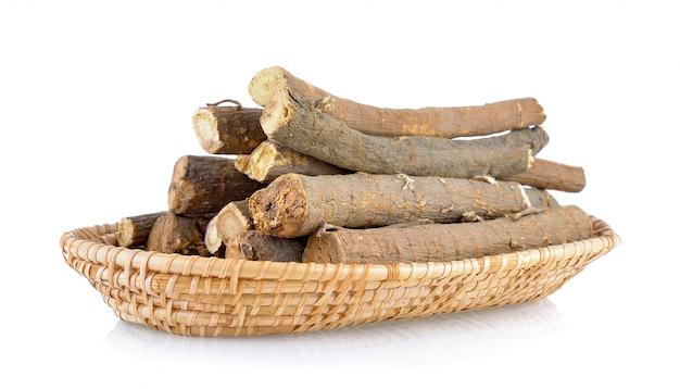 Süßholzwurzeln im korb auf weißem hintergrund