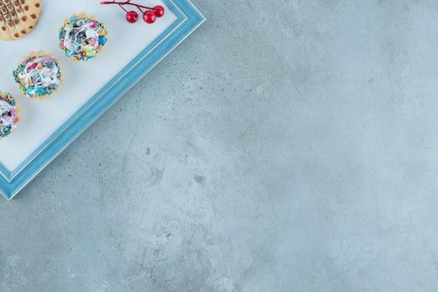 Süßigkeit cupcakes, ein keks und eine weihnachtsbeerendekoration auf einem brett auf marmorhintergrund. hochwertiges foto