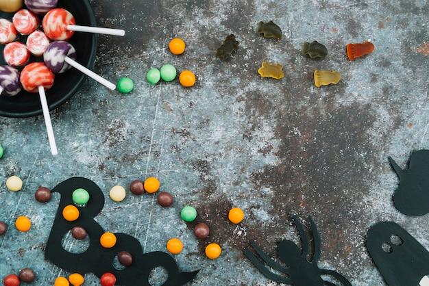 Süßigkeit und dekorative halloween-attribute auf rändern
